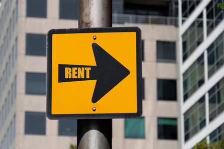 Directional yellow sign with conceptual message RENT on black arrow over defocused office building background. Stock Photo
