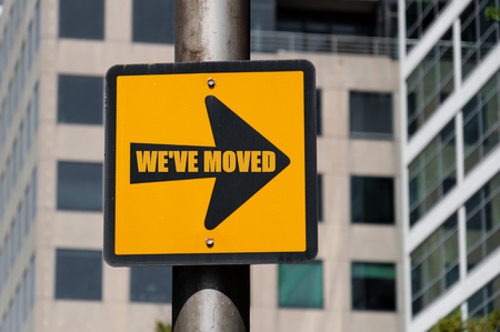Directional yellow sign with conceptual message WE HAVE MOVED on black arrow over defocused office building background.