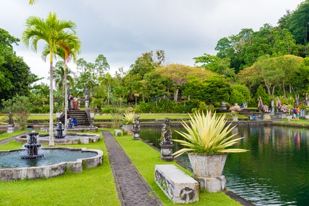 spiritual architecture: Bali, Indonesia - May 3, 2017 : Tirta Gangga, the former royal water palace is a maze of pools and fountains surrounded by a lush garden and stone carvings and statues near Karangasem, Bali, Indonesia