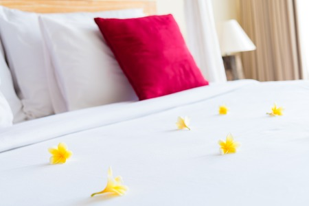 Hotel room with bed and flower arrangement, copy space for text Stock Photo