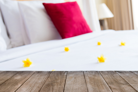 confortable: Perspective empty wooden table in front of hotel room with bed and flower arrangement. Template for product presentation display. Empty space for product placement. Tourism industry concept Stock Photo