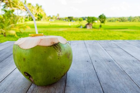Green young coconut with straw on table, rice fields and coconut trees in backgroud. Copy space available