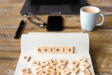 Closeup on notebook over wood table background, focus on wooden blocks with letters making Hotels word. Business concept image. Laptop, glasses, pen and mobile phone in a defocused background.