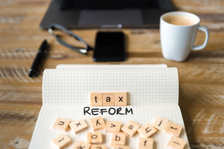 Closeup on notebook over vintage desk surface, front focus on wooden blocks with letters making Tax Reform text. Business concept image with office tools and coffee cup in background