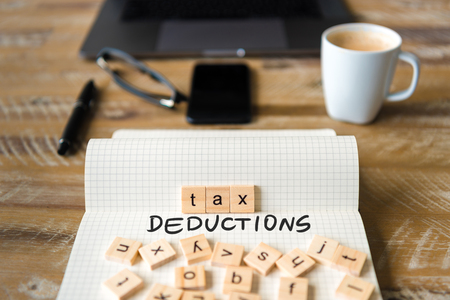 Closeup on notebook over vintage desk surface, front focus on wooden blocks with letters making Tax Deductions text. Business concept image with office tools and coffee cup in background