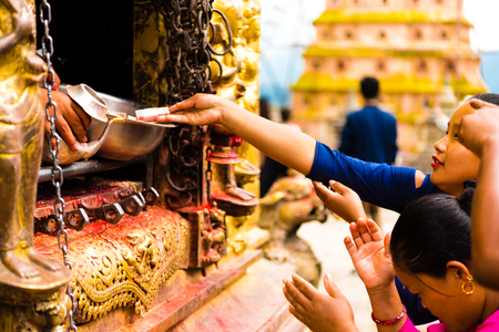 Kathmandu, Nepal - July 15, 2018 : People praying at the Monkey temple Swayambhunath Stupa complex, a UNESCO heritage site and an important place of worship for Buddhists Editorial