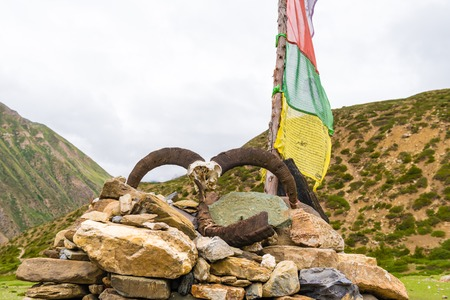 Manang village, Annapurna Conservation Area, Nepal - July 26, 2018 : Traditional buddhist prayer flags over foggy mountain background are used to bless the surrounding countryside and to promote peace Editöryel