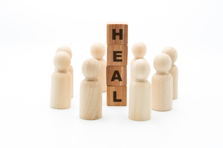Wooden figures as business team in circle around word HEAL, isolated on white background, minimalist concept