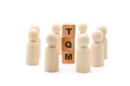 Holzfiguren als Business-Team im Kreis um das Akronym TQM Total Quality Management, isoliert auf weißem Hintergrund, minimalistisches Konzept