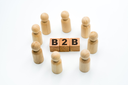 Wooden figures as business team in circle around acronym B2B Business To Business, isolated on white background, minimalist concept