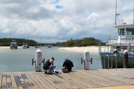 Huskisson, NSW, Australia-December 22, 2018: Fishermen on public wharf in the city of Huskisson, NSW, Australia, a small coastal town well known as gateway to Jervis Bay area