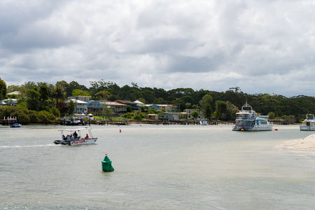 Huskisson, NSW, Australia-December 22, 2018: View over bay of water and boats from the public wharf in the city of Huskisson, Australia, a small coastal town well known as gateway to Jervis Bay area 報道画像