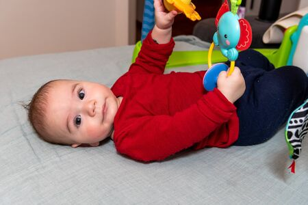 Adorable 6 months old little baby boy on his back surrounded by colourful toys