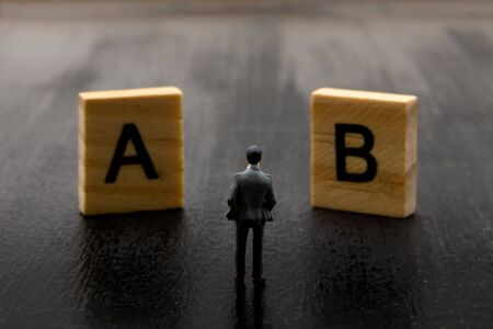 Miniature figurine posed as businessman making decision on Solution A versus B, minimalist abstract concept image Stock fotó