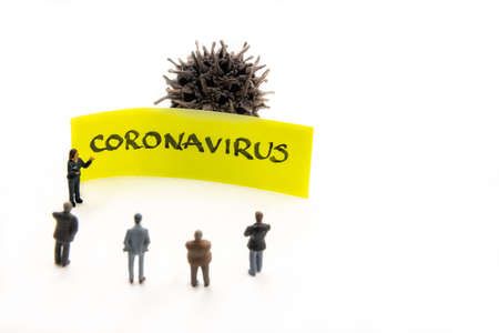 Meeting with miniature figurines posed as business people standing around sticky note with Coronavirus handwritten message in background, minimalist abstract concept with focus on text Stock Photo