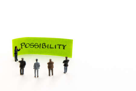 Meeting with miniature figurines posed as business people standing around sticky note with Possibility handwritten message in background, minimalist abstract concept with focus on text