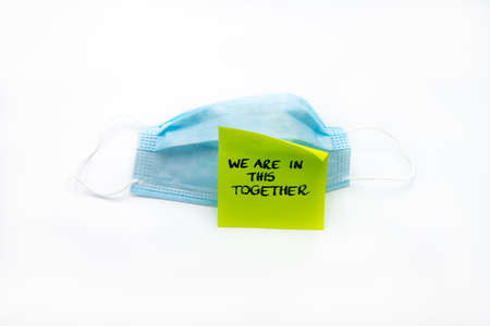 Single use medical face mask with handwritten message on post-it note We Are In This Together isolated over white background, coronavirus protection concept Zdjęcie Seryjne