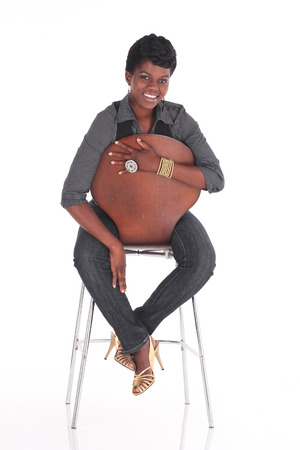 sitting pretty: African  female in casual uniform sitting down on a chair Stock Photo