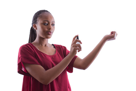 African woman with braids in a red shirt is trying a new perfume on an isolated white background
