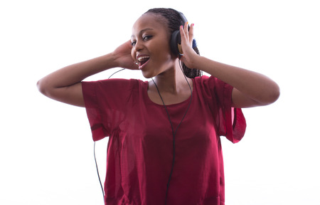 afro woman: African woman with braids is happily listening to music through earphones on an isolated white background