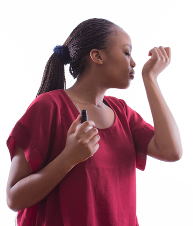 perfume woman: African woman with braids in a red shirt is trying a new perfume on an isolated white background