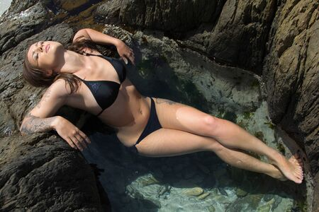 desirable: Gorgeous bikini girl with tattoo sitting in a Rock Pool with her eyes closed