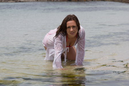 sopping: Gorgeous female at the beach crawling in water sopping wet