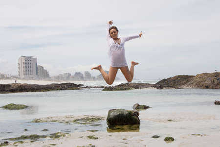 beach babe: Exciteable woman in shirt jumping mid motion at the beach