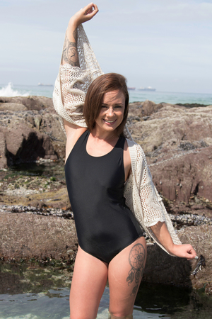 informal clothing: Beautiful swimsuit model in full piece standing in the sea smiling for the camera
