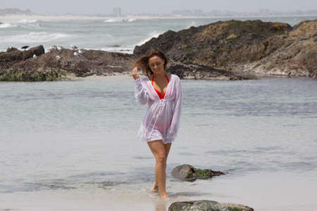 beach babe: Gorgeous girl walking along the beach shore in bikini and shirt smiling Stock Photo