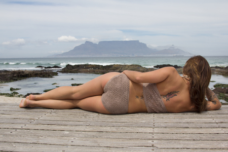 Back view of tattooed bikini babe lying down and looking at the ocean with Table Mountain in the background Stock Photo