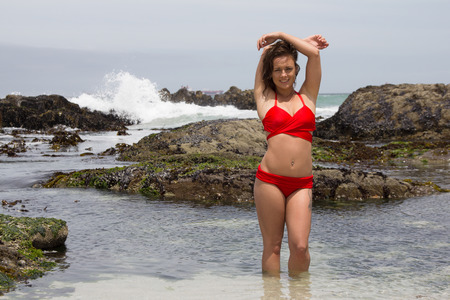 Pretty girl in a red bikini posing and smiling for the camera at the Seaside