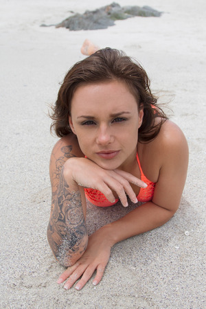 beach babe: Hot Babe lying in the sand on the beach looking at the camera Stock Photo