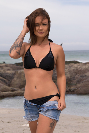 beach babe: Sexy bikini babe with tattoos taking off her shorts at the beach