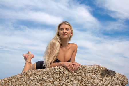 blonde haired: A beautiful blonde haired woman lying on a rock at the beach in her one piece looking at the camera and smiling