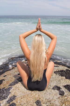 backview: Back-view of beautiful Blonde in her swimwear practising yoga with the beach in front of her Stock Photo