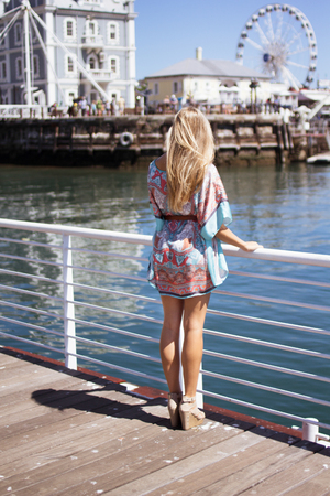 backview: Back-view of an attractive blonde woman standing on a walkway looking out over the docks