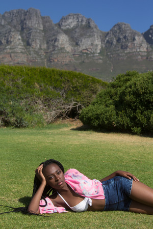 desirable: A gorgeous african female in summer style clothing lying in a field with the mountain behind her