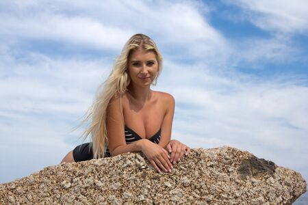 blonde haired: A beautiful blonde haired woman lying on a rock at the beach in her one piece looking at the camera seductively