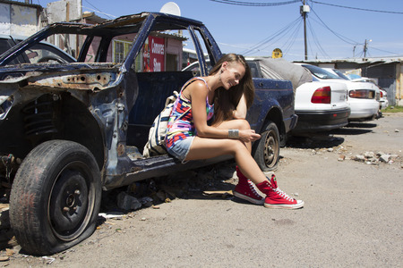 beaten up: Female sitting on an old beaten up car reading a message on her cell phone