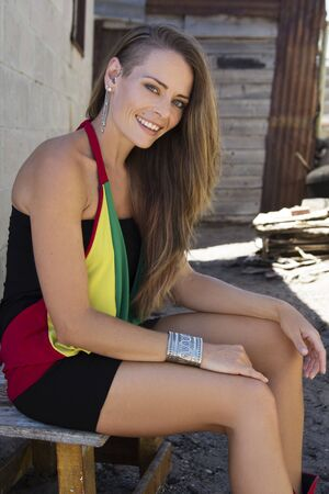 Caucasian female sitting outside of a shack in an African township smiling Stock Photo