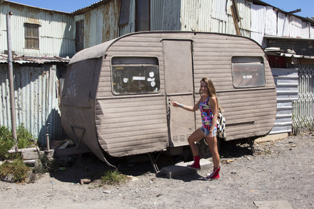 beaten up: Female checking if anyone is home in an old beaten up caravan in an African township