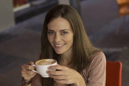 Caucasian female sitting outdoors drinking coffee Stock Photo