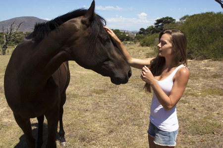 farm girl: Farm girl meeting and greeting a horse in a meadow