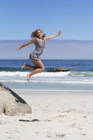 Female jumping off a rock at the beach
