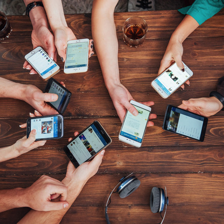 Top view hands circle using phone in cafe - Multiracial friends mobile addicted interior scene from above - Wifi connected people in bar table meeting - Concept of teamwork