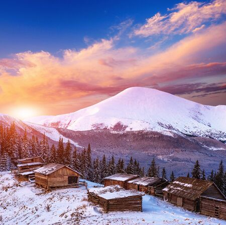 sunrises: cottage in snowy mountains Stock Photo