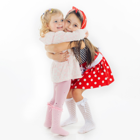 sisters hugging isolated on white background