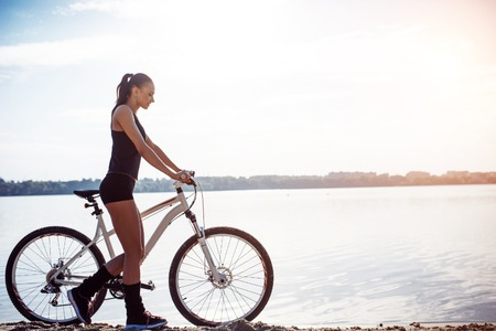 woman on a bicycle near the water Stock Photo