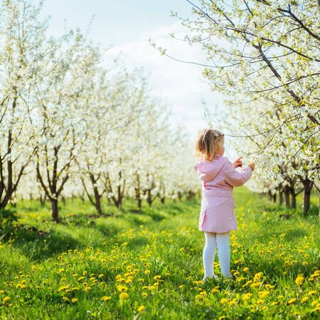child outdoors in the blossom trees. Art processing and retouchi